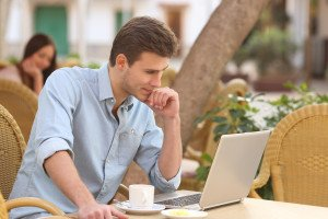 Self employed man concentrated while is working with a laptop in a restaurant terrace